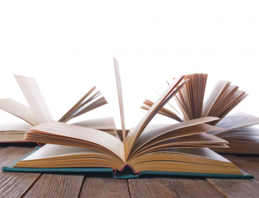 En bog ligger opslået på et bord