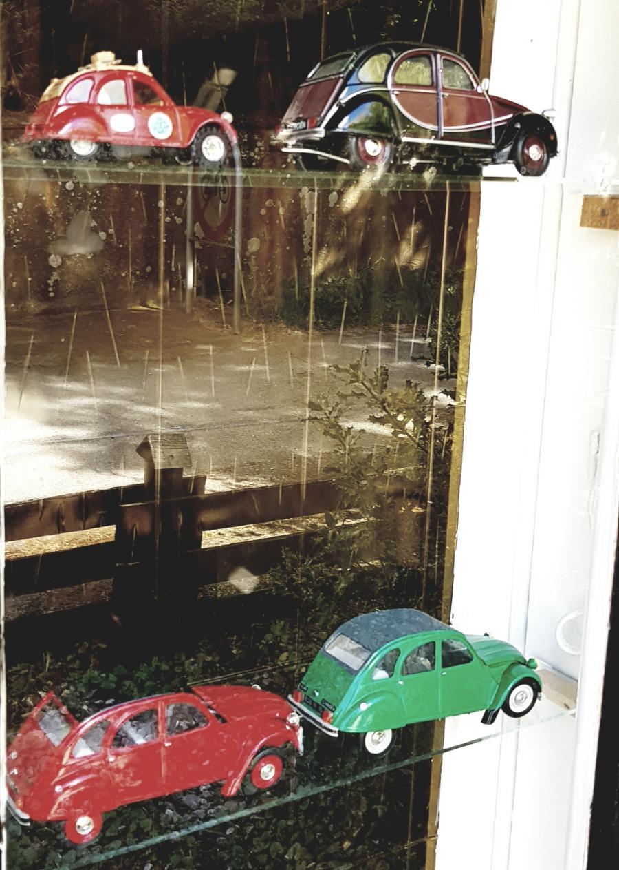 Miniature udgaver af 2CV biler i en udstillingsmontre