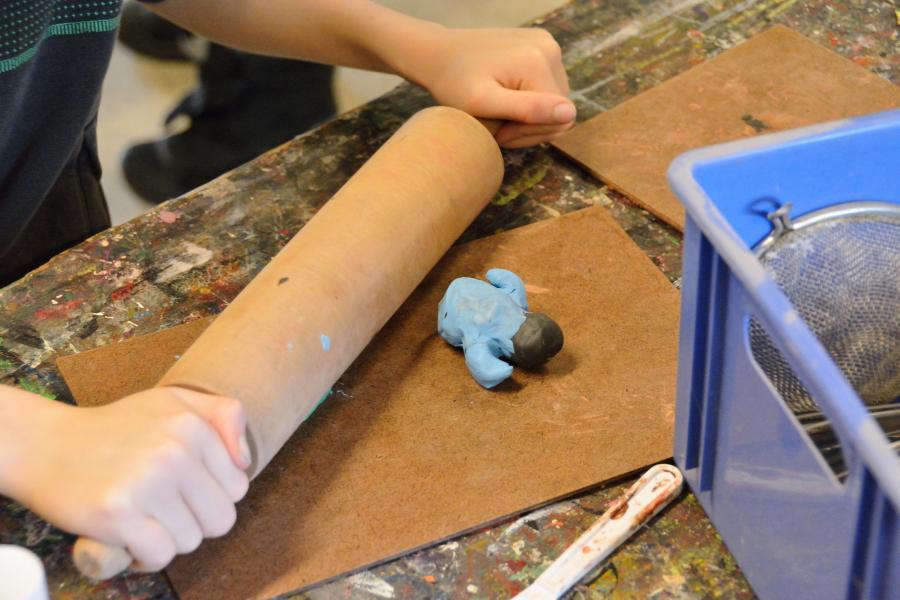 Barn ruller modellervoks ud på et bord